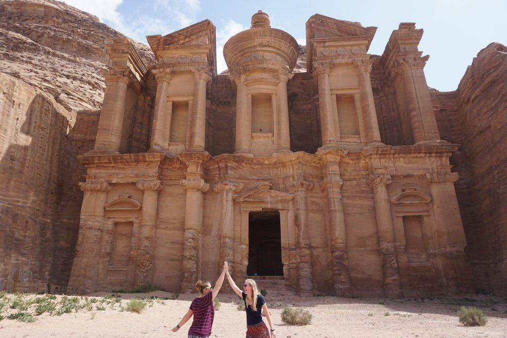 high fiving a friend after surviving the hike to the Monastery in Petra, Jordan